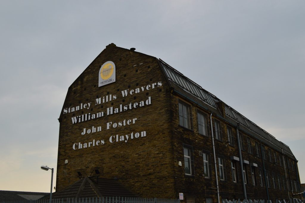 Home to 'Oxbridge Flannel' & John Foster: Stanley Mills, a large brick building stands tall against a moody blue sky